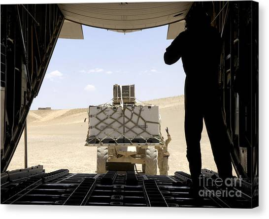 Forklifts Canvas Print - A Forklift Loads Cargo Onto A C-130 by Stocktrek Images