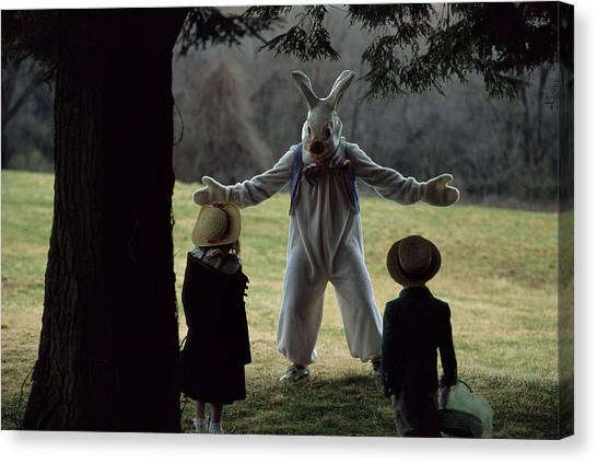 Easter Baskets Canvas Print - A Rabbit Meets Two Children During An by Joel Sartore