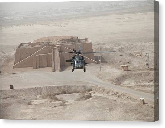 A Us Army Black Hawk Helicopter Hovers Canvas Print by Everett