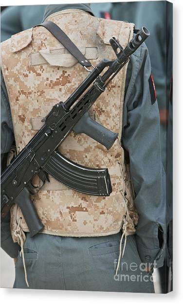 Ak-47 Canvas Print - An Ak-47 Rests On The Sling Of An by Terry Moore