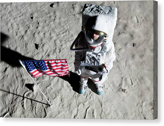Space Suit Canvas Print - An Astronaut On The Surface Of The Moon Next To An American Flag by Caspar Benson