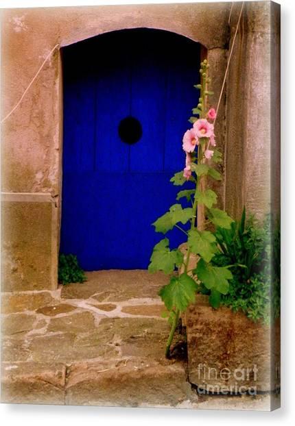 Blue Door And Pink Hollyhocks Canvas Print