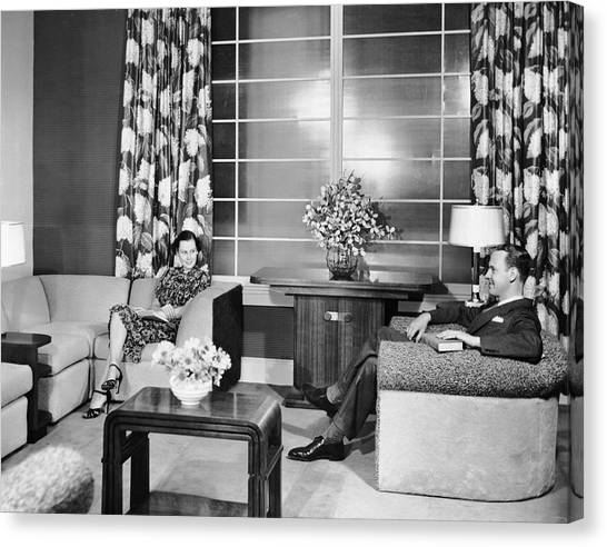 Couple Sitting In Living Room Reading Canvas Print by George Marks