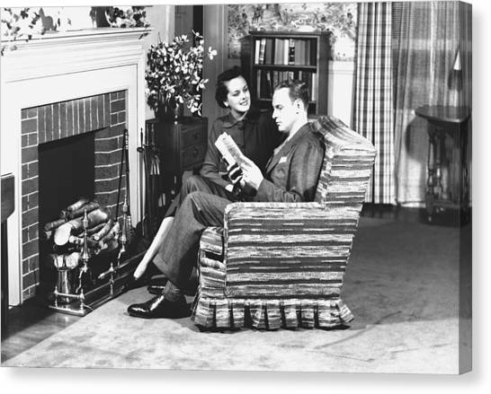 Couple Sitting On Armchair In Front Of Fireplace, (b&w) Canvas Print by George Marks