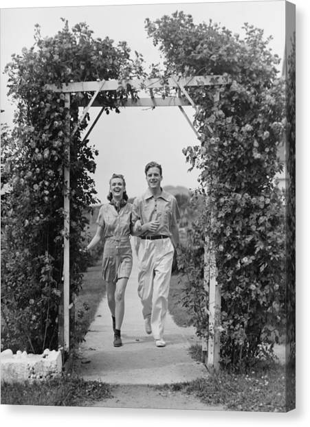 Couple Walking On Footpath Towards Rose Covered Pergola, (b&w) Canvas Print by George Marks