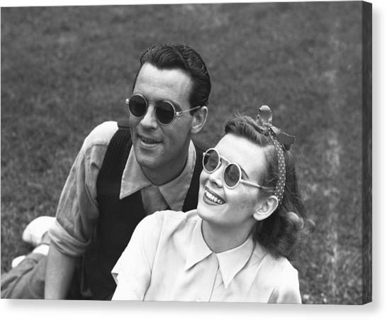 Couple Wearing Sunglasses Sitting On Grass, (b&w) Canvas Print by George Marks
