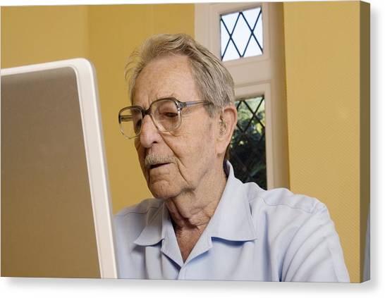 Elderly Man Using A Laptop Computer Canvas Print by Steve Horrell