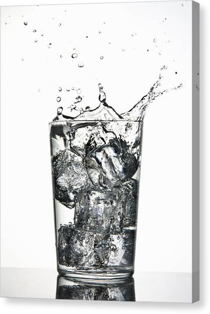 Water Canvas Print - Ice Cubes Splashing Into Fizzy Drink by Walter Zerla
