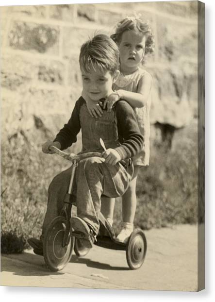Little Boy Giving Little Girl Ride On Tricycle Canvas Print by George Marks
