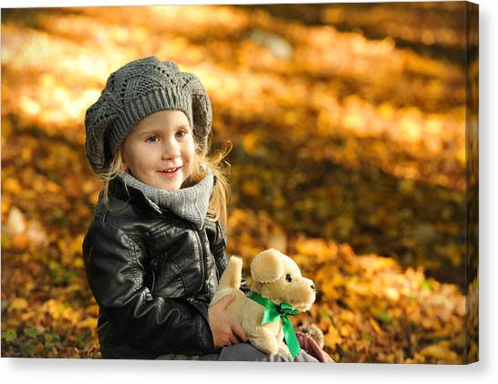 Little Girl In Autumn Leaves Canvas Print by Waldek Dabrowski