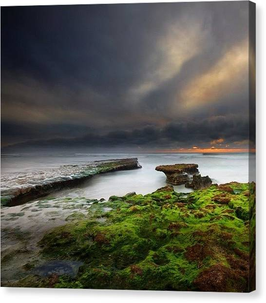 Long Exposure Of A Stormy Sunset At A Canvas Print by Larry Marshall