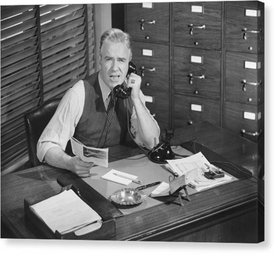 Man Sitting At Desk, Talking On Phone, (b&w), Elevated View Canvas Print by George Marks