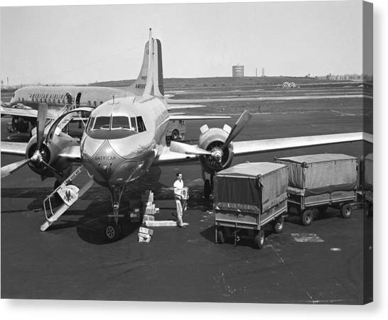 Man Standing At Airplane On Runway, (b&w) Canvas Print by George Marks