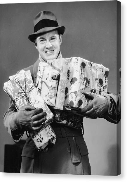 Man With Coat, Gloves And Hat Carrying Christmas Gifts Canvas Print by George Marks