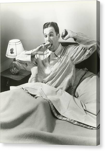Mature Man Yawning Sitting In Bed Canvas Print by George Marks