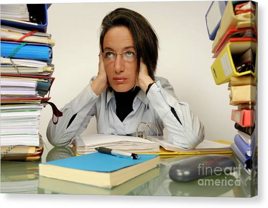 Mature Office Worker Sitting At Desk With Piles Of Folders Canvas Print by Sami Sarkis