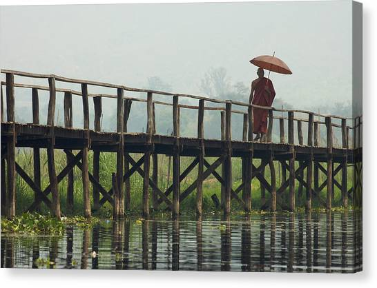 Monk Crosses A Bridge On The Eastern Shore Town Canvas Print by David Greedy
