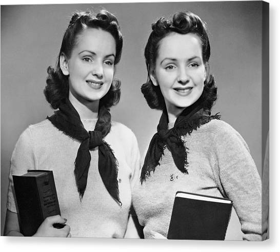 Portrait Of Teenaged Twin Girls Holding Books Canvas Print by George Marks
