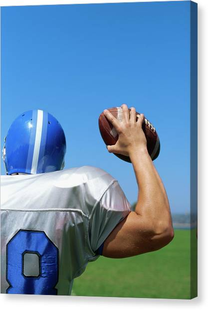 Rear View Of A Football Player Throwing A Football Canvas Print by Stockbyte