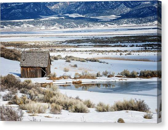 Rustic Barn In A Snowy Valley Next To A Pond Canvas Print by C Thomas Willard