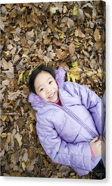 Smiling Girl Lying On Autumn Leaves Canvas Print by Ian Boddy
