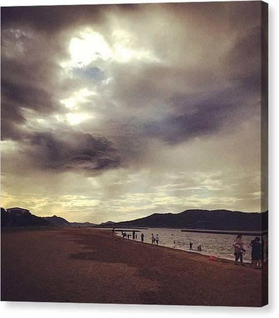 Beach Sunsets Canvas Print - Sun Breaks Through Rainy Clouds On The Beach by Aldo Bloise
