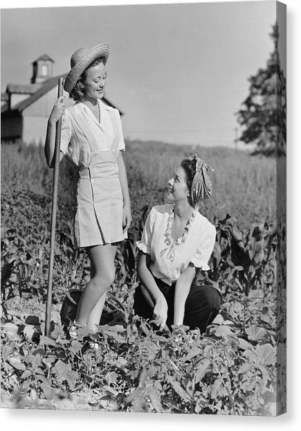 Two Women Gardening In Field Canvas Print by George Marks