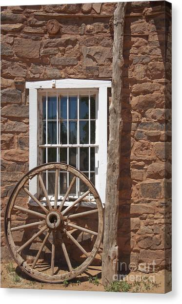 Window In Stone Building With Wagon Wheel Canvas Print by Thom Gourley/Flatbread Images, LLC