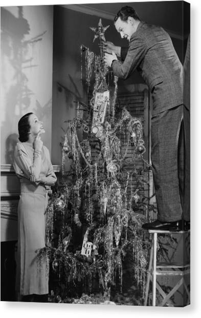 Woman Assisting Man Placing Star On Top Of Christmas Tree, (b&w) Canvas Print by George Marks
