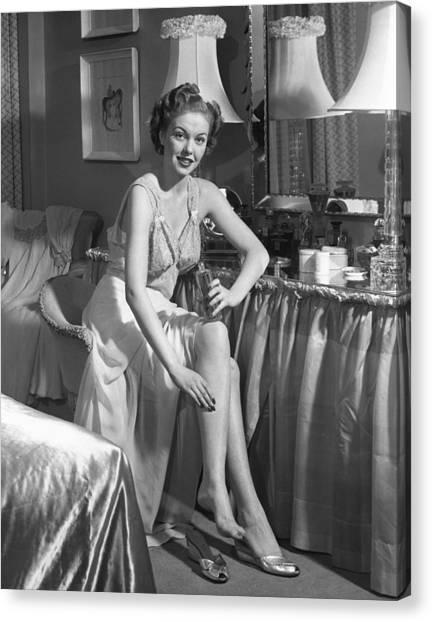 Woman In Bedroom Putting On Lotion Canvas Print by George Marks