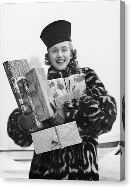 Woman In Fur Coat Holding Christmas Gifts Canvas Print by George Marks