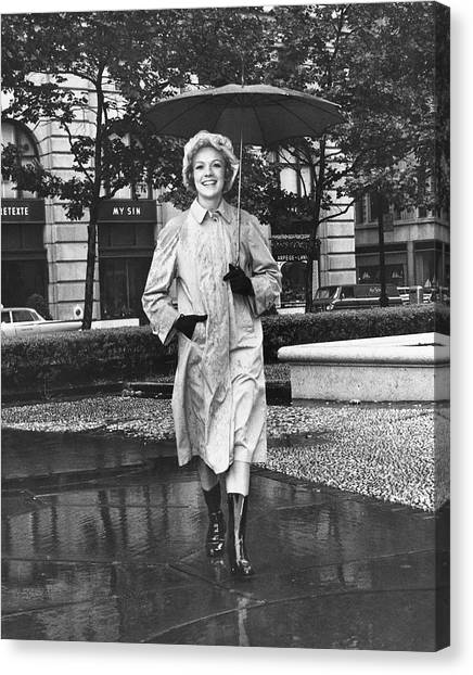 Woman Walking In Rain Canvas Print by George Marks