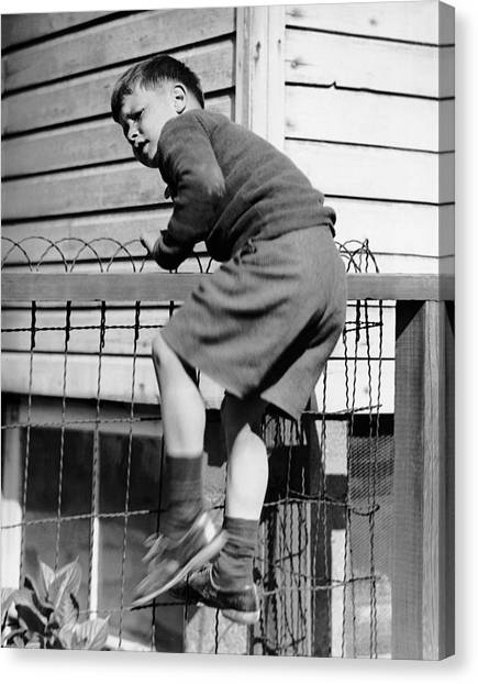 Young Boy Climbing Fence Canvas Print by George Marks