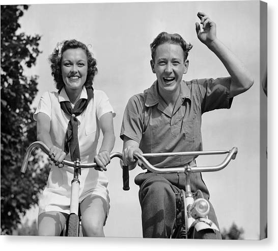 Young Couple Riding Bicycles Canvas Print by George Marks