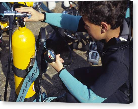 Young Scuba Diver Checking Kit Canvas Print by Alexis Rosenfeld