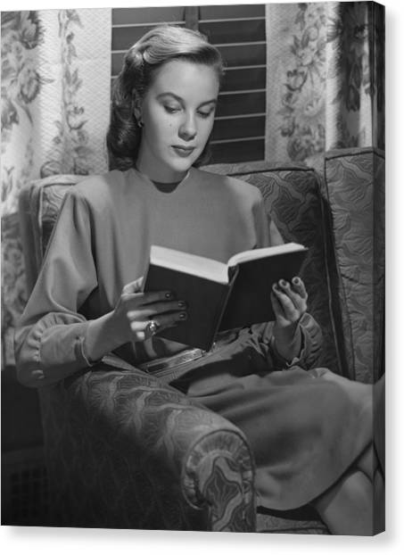 Young Woman Sitting On Sofa, Reading Book, (b&w) Canvas Print by George Marks