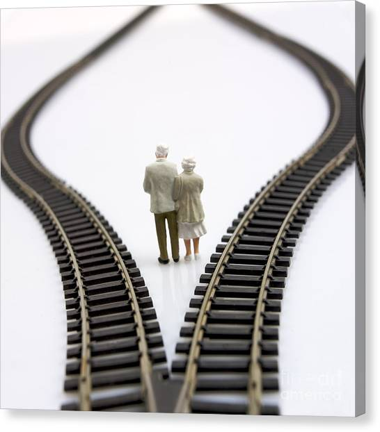 Worried Canvas Print - Figurines Between Two Tracks Leading Into Different Directions Symbolic Image For Making Decisions. by Bernard Jaubert