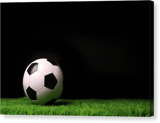 Soccer Canvas Print - Soccer Ball On Grass Against Black by Sandra Cunningham