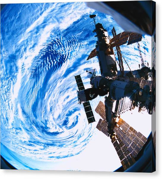 Space Shuttle Canvas Print - A Space Station Orbiting Above Earth by Stockbyte