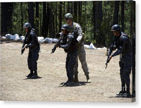 Green Berets Canvas Print - A Green Beret Instructs Tigres Trainees by Stocktrek Images