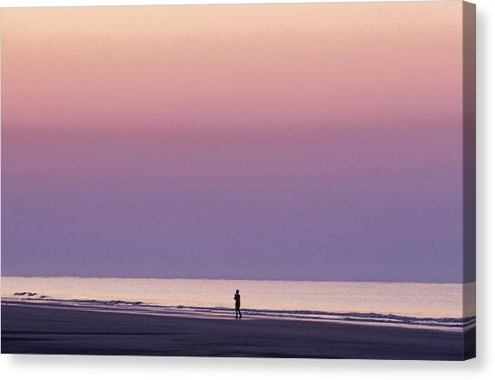 Sunrise Horizon Canvas Print - A Person Walks On The Beach At Sunrise by Kenneth Garrett