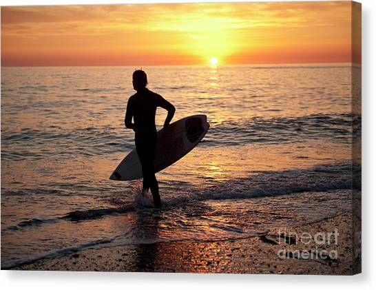 A Young Man Surfing At Sunset Off Aberystwyth Beach, Wales Uk Canvas Print