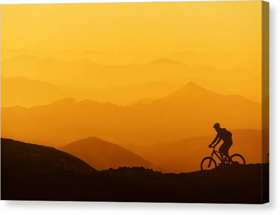 Biker Riding On Mountain Silhouettes Background Canvas Print