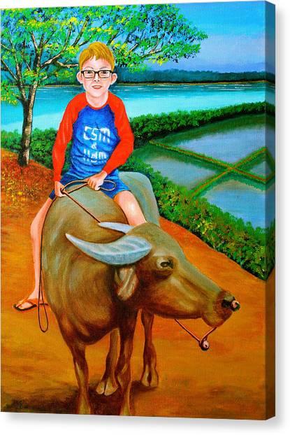 Boy Riding A Carabao Canvas Print