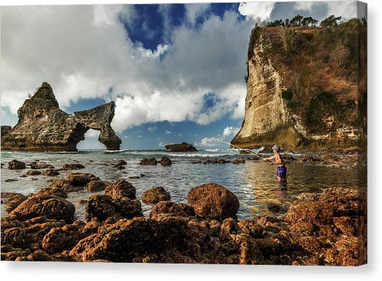 Canvas Print featuring the photograph catching fish in Atuh beach by Pradeep Raja Prints