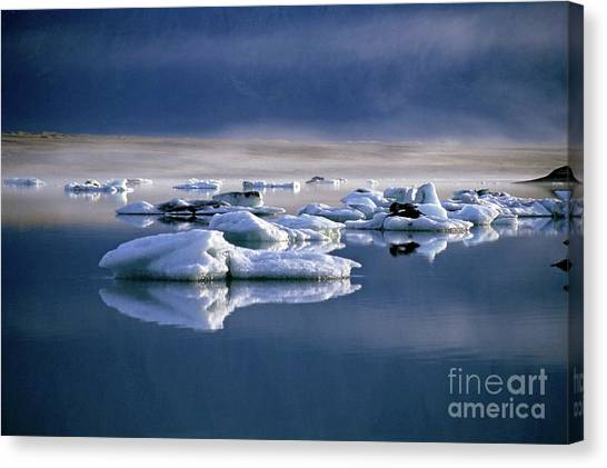 Floating Icebergs Reflected In The Quiet Waters Of Jokulsarlon Canvas Print by Sami Sarkis