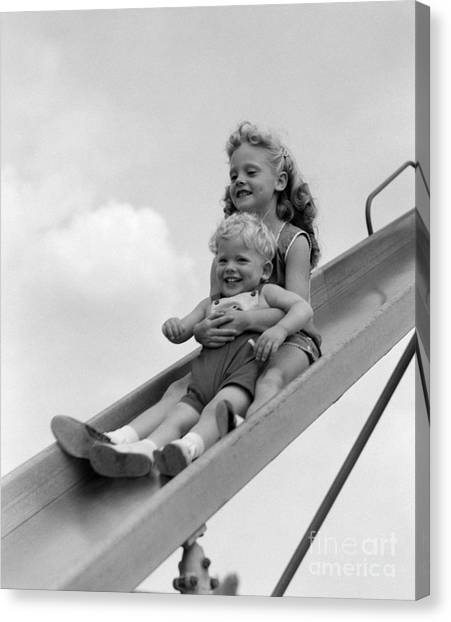 Big Sister Canvas Print - Girl And Little Boy Going Down Slide by H. Armstrong Roberts/ClassicStock