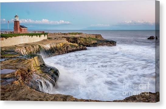 Long Exposure Of Waves Against The Cliff With Lighthouse In Shot Canvas Print