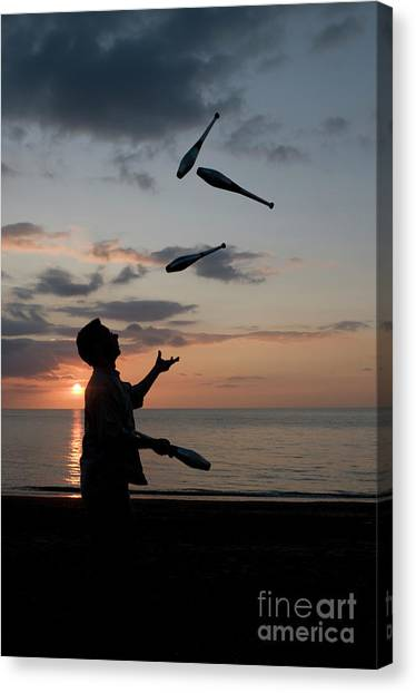 Man Juggling With Four Clubs At Sunset Canvas Print