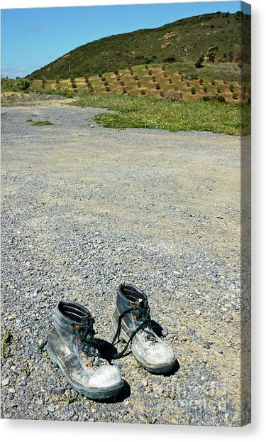 Old Pair Of Worn Out Boots Sitting On Stony Asphalt Canvas Print by Sami Sarkis